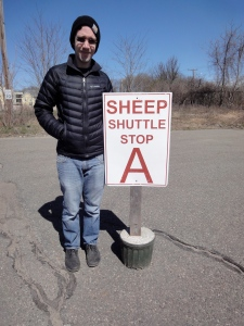 Ben standing next to a sign that reads Sheep Shuttle Stop